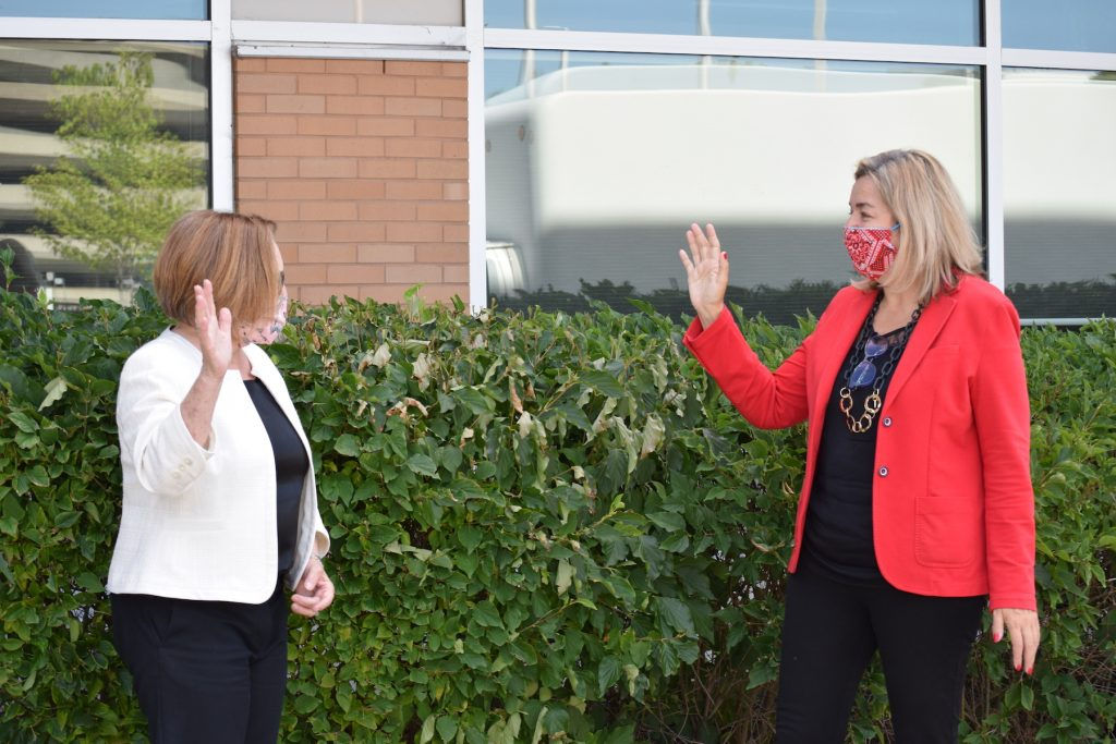 two school officials greet each other from a distance outdoors, wearing masks