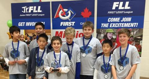 A lower school lego league poses with medals