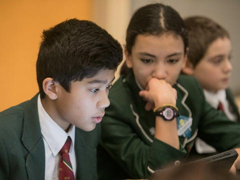 prep school students look at a computer together