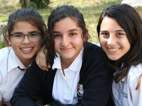 three upper school students smiling together