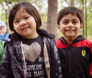 two smiling preschool students in the outdoors