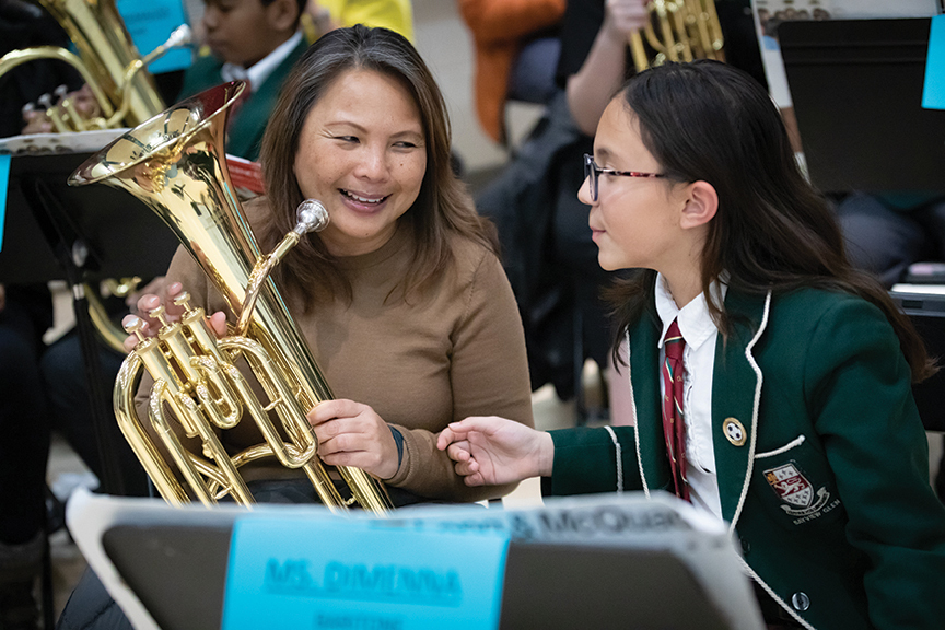 a student shows her mother how to play the euphonium at a music event