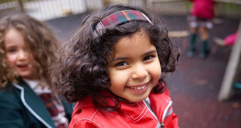 a smiling preschool student wearing a red jacket